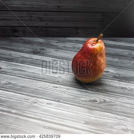 A Bright Ripe Pear Stands On A Gray Plank Surface. Red-yellow Shiny Peel. Close-up. Copy Space. Side