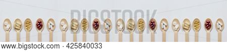 Dietary Supplements And Vitamins On Wooden Spoons On A White Background. The Concept Of A Healthy Li