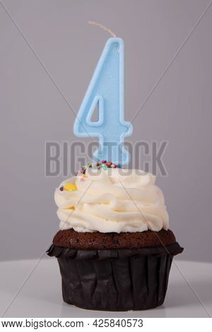 Tasty Chocolate Cupcake With White Topping Cream And Candle In Shape Of Number Four 4. On A White St