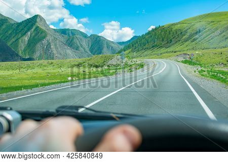 Landscape Of A Valley Among High Mountains With An Asphalt Road On Which The Car Is Driving, A View