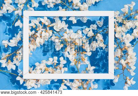 White Acacia Flowers In Blue Transparent Water With White Frame. Summer Floral Composition With Sun