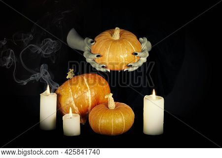 Samhain Pagan Ritual. Hedge Witches Pale Hands With Black Sharp Nails Among Pumpkins And A Burning C