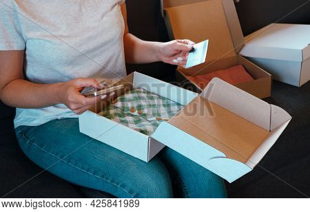 Online Shopping Using The Application On The Phone. A Woman Sits In Bed Unpacks An Order And Holds A