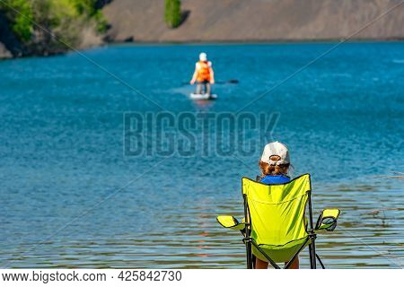 Rear View, A Little Girl, A Teenager, A Child, Sitting On A Camping Tourist Chair And Watching Her S