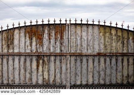 Old rusty gate in an abandoned house. Broken gate.