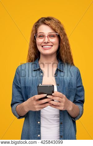 Optimistic Blond Female In Denim Shirt Smiling And Looking At Camera While Browsing Smartphone Again
