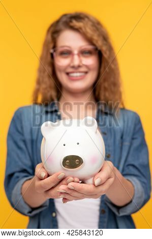 Soft Focus Of Optimistic Young Blond Female Demonstrating Piggy Bank With Money While Making Savings