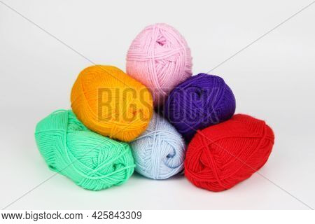 A Lot Of Multi-colored Wool Balls Made Of Wool Yarn Lie In The Form Of A Pyramid Close-up On A White