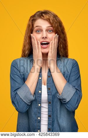 Young Curly Haired Ginger Female In Casual Outfit Keeping Hands On Cheeks And Looking Surprised Whil