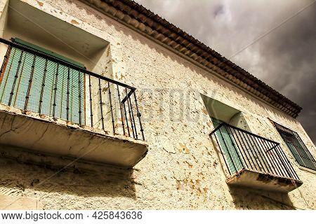 Old House Facade With Rusty Balcony And Green Blind. Alcaraz Village, Castilla La Mancha, Spain.