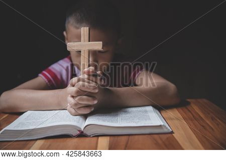 Boy Hands Holding A Holy Cross And Praying To God, Child Praying For God Religion.