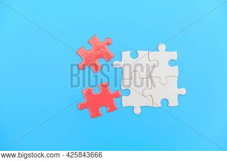 Jigsaw Puzzle On A Blue Background. Completing Final Task, Missing Jigsaw Puzzle Pieces And Business
