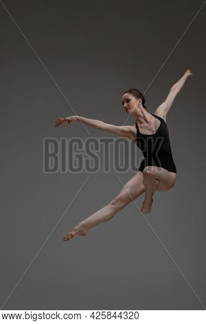 Professional Leaping Ballerina Dancing Against Gray Background