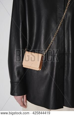 Beige Leather Embossed Crossbody Wallet On A Golden Chain. Person In Black Leather Jacket. Small Lea