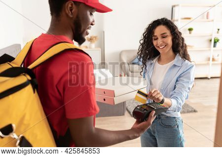 Smiling Deliveryman Holding Pos Machine, Woman Paying With Card