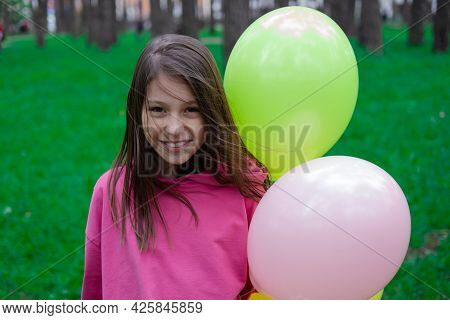 Pretty Tween Teenager Brunette Girl In Pink Holding Colorful Hot Air Balloons Outdoors. Party, Birth