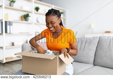Online Delivery Service. Cheerful African American Woman Unpacking Parcel Box With Purchase At Home