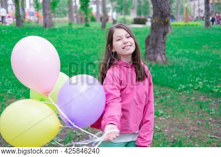 Sweet Tween Brunette Girl In Pink Holding Colorful Balloons Outdoors. Party, Birthday Concept. Summe
