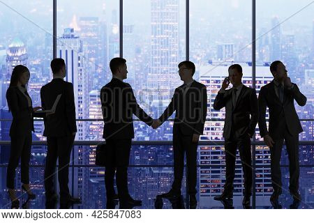 Backlit Businesspeople Standing In Panoramic Office Interior With City View. Teamwork And Conference