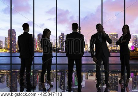 Backlit Businesspeople Standing In Panoramic Office Interior With City View. Team Work And Success C