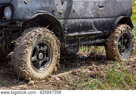 Black Suv With Big Wheels Dirty In A Swamp Stands On The Grass, The Water Flows From The Body After