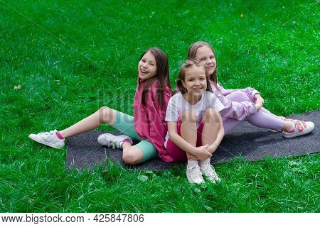 Three Beautiful Happy Tween Teenagers Girls In Colorful Clothes Sitting On Green Grass In Park. Summ