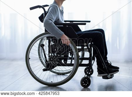 Disability In Teenagers Concept. Side View Of Unrecognizable Impaired Teen Boy Sitting In Wheelchair