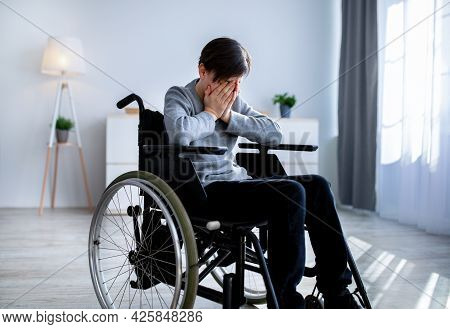 Depression In Disabled Teenagers. Unhappy Handicapped Teen Boy In Wheelchair Crying At Home