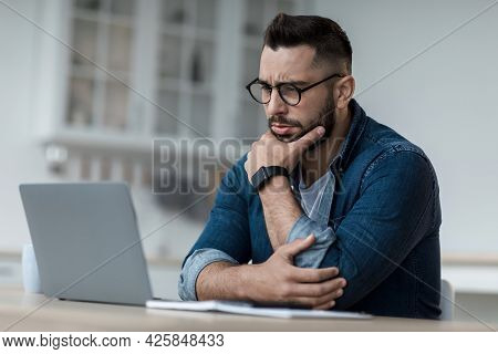 Thoughtful Businessman Think Of Online Project, Look At Laptop At Workplace, Professional Consider S