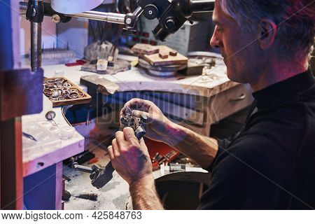 Jewelry Maker Working With Gem-cutting Tool For Amethyst Grinding
