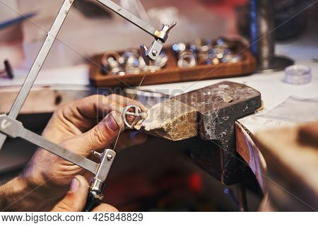 Craftsman Using Fretsaw For Cutting Steel Jewelry Product
