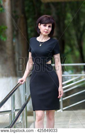 Strict Brunette In A Black Dress Near Office Building On The Street.