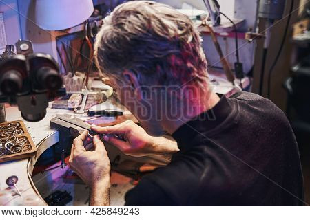 Jewelry Craftsman Using Hand File While Working On Product