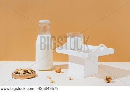 Glass With Vegan Milk From Various Nuts  On White Wooden Tray On Sunlit Background. Dairy And Lactos