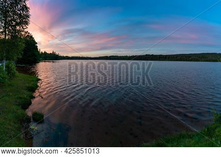 Beautiful Summer Sunset Over A Calm And Idyllic Lake With Forest Reaching To The Lake Shore