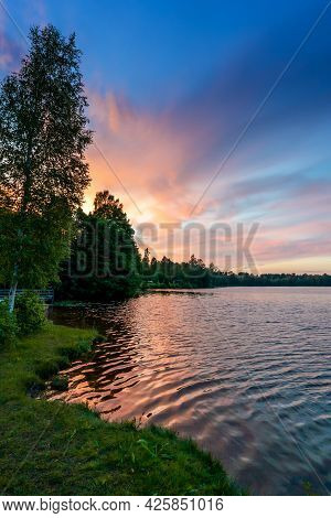 Vertical View Of A Beautiful Summer Sunset Over A Calm And Idyllic Lake With Forest Reaching To The