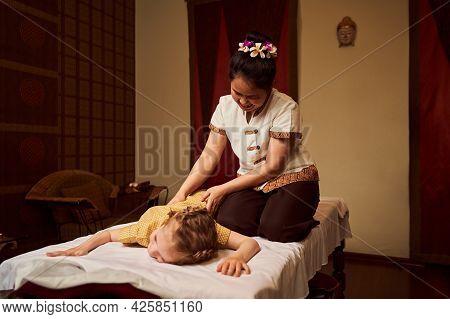 Girl At Massage Session. Spa Salon And Masseuse