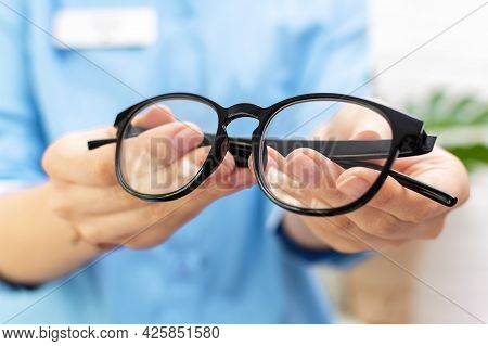 Doctor Optometrist In Blue Uniform Holds In Her Hands And Gives A Pair Of Black Rimmed Glasses To A