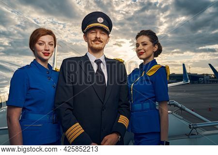 Smiling Pilot And Charming Stewardesses Standing On The Boarding Stairs