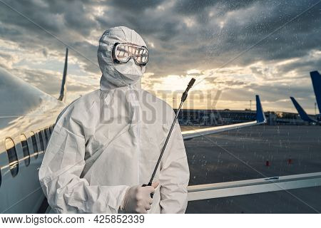 Worker In A Hazmat Suit Spraying A Disinfectant In The Air