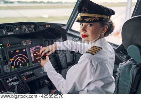 Lady Pilot Posing For The Camera In The Cockpit