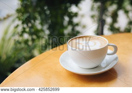 Cup Of Coffee With Latte Art On A Wooden Table In A Cafe. Place For Text.