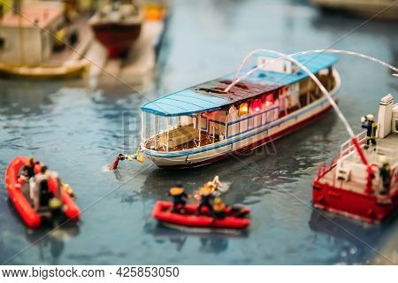 Miniature People. Miniature Models Of Firefighters Extinguish A Fire On A Boat On The Water. Miniatu