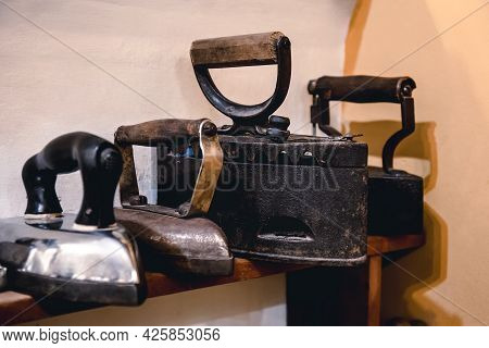 Collection Of Vintage Irons For Ironing Clothes. Antique Metal Irons, A Museum Piece Of Antique Hous