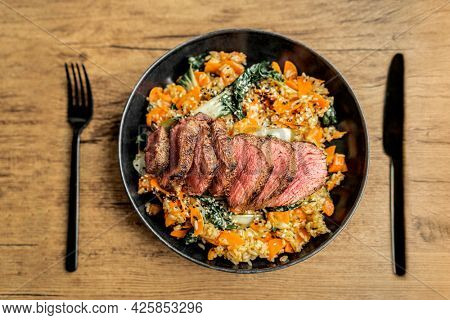 Home cooking steak meal top view on wooden table. Savoury sauteed vegetables in stir fry rice topped with sirloin steak.
