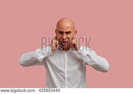 Horizontal Portrait Of Irritated Bald Guy With Bristle Plugs Ears, Ignores Loud Swearing Neighbors.