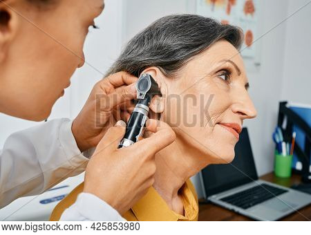 Hearing Test For Mature People, Otoscopy. Otolaryngologist Doctor Checking Senior Womans Ear Using O