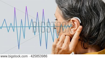 Hearing Aids. Senior Woman Wearing Behind The Ear Hearing Aid With Sound Waves Pattern In Foreground