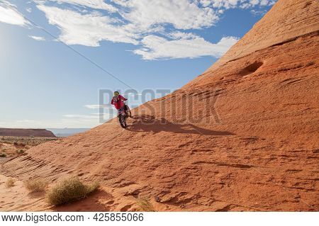 Page, Arizona, Usa - October 31, 2014:  A Young Man On A Motorcycle Quickly Climbs Up A Steep Sandst
