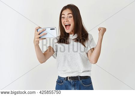 Young Woman Winning In Video Game On Smartphone, Scream Yes With Joy And Satisfaction, Standing Over